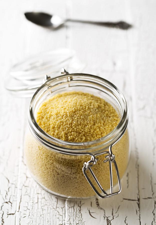 Rozsypisko surowy, uncooked couscous w szklanym słoju na drewnianym stole, fotografia royalty free