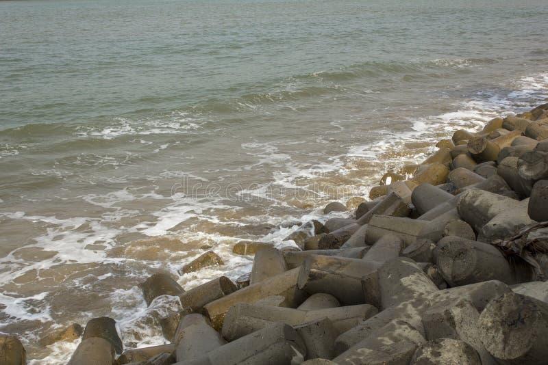 Rozsypisko szarość betonuje tetrapods, tsunami bariera w turkusowych dennych falach, obrazy royalty free
