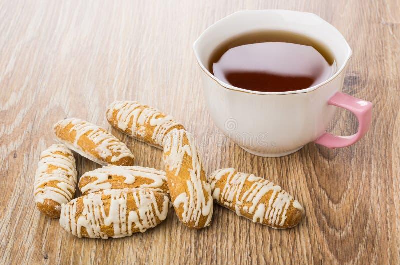 Rozsypisko warzący oszkleni ciastka, filiżanka herbata na stole zdjęcie royalty free