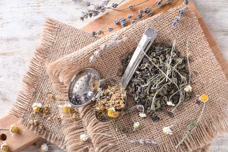 Rozsypisko wysuszony chamomile i liście z herbacianym durszlakiem na drewnianym stole obrazy royalty free