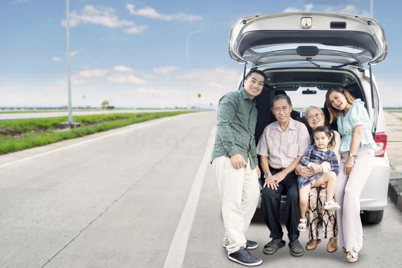 Rozszerzony szczęśliwy rodzinny obsiadanie na samochodowym bagażniku zdjęcie royalty free