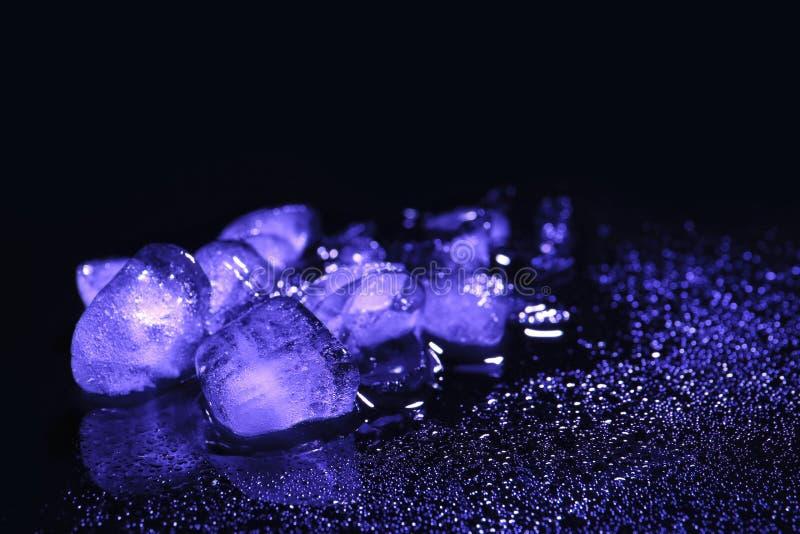 Roztapiający kostka lodu i wod krople na czarnym tle obrazy royalty free