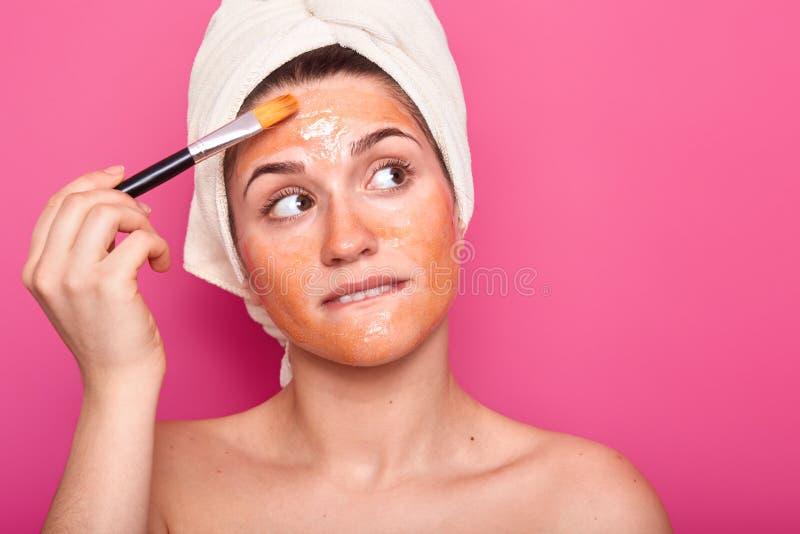 Rozważni Europejscy młoda kobieta kąski obniżają wargę, skupiającą się na boku, stosowali piękno maskę, używają kosmetyka muśnięc obraz stock