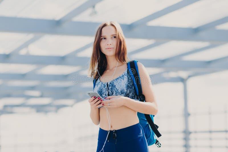 Rozważna ładna młoda kobieta z zdrową czystą skórą, ubierającą w przypadkowym wierzchołku i leggings, torbę, trzyma nowożytnego e fotografia stock
