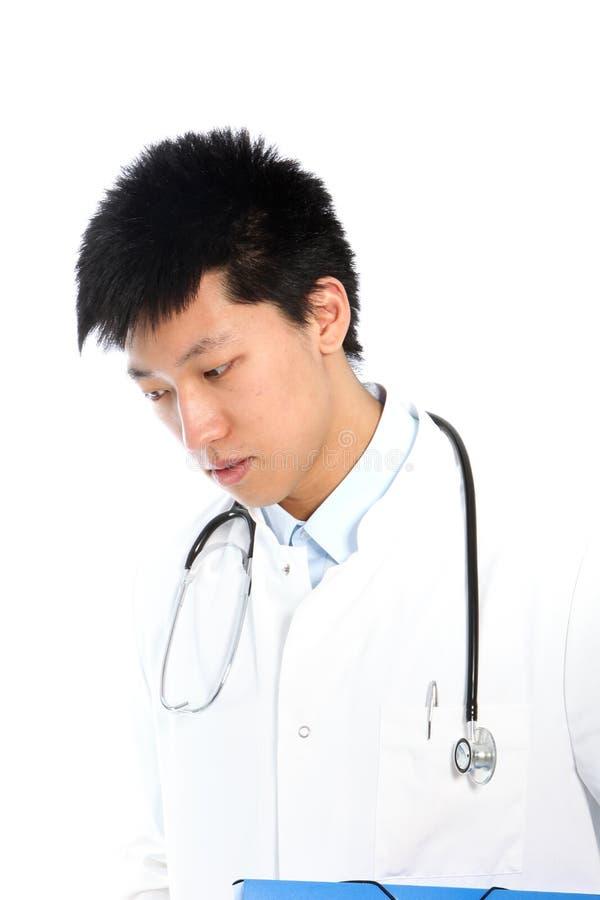 Rozważna Azjatycka młoda samiec lekarka patrzeje w dół fotografia stock