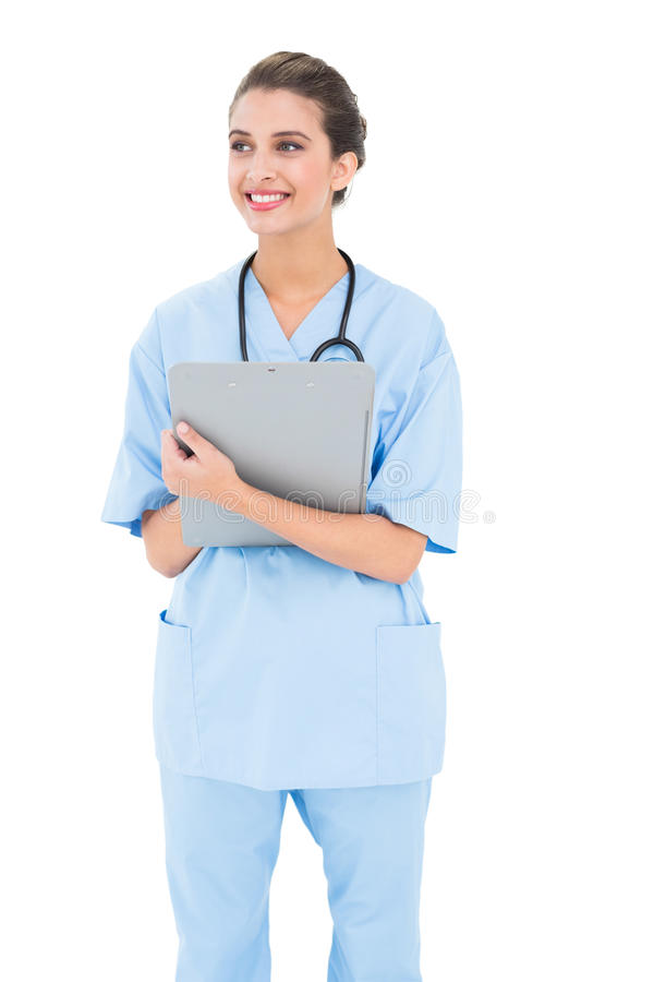 Rozważna brown z włosami pielęgniarka w błękicie szoruje trzymać schowek obraz stock