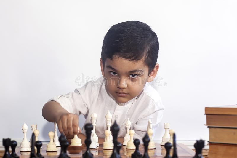 Rozważna chłopiec bawić się szachy Troszkę bawić się szachy bliskowschodnia chłopiec Myśleć dalej znajduje najlepszy ruch fotografia stock
