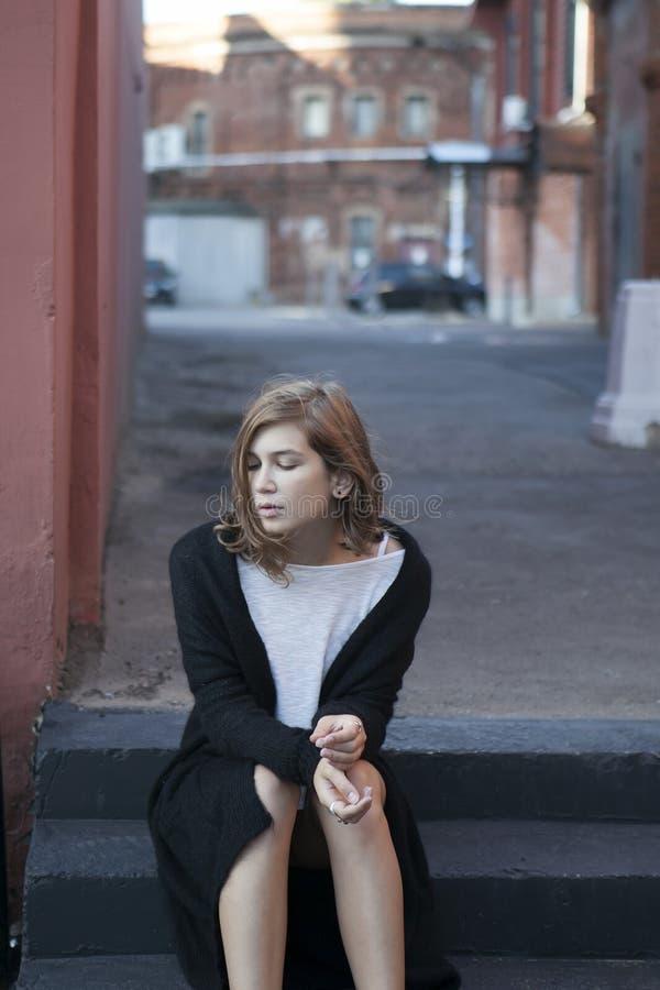 Rozważna dziewczyna w długim czarnym kardiganie i skrótów skrótach siedzi na krokach zdjęcia royalty free