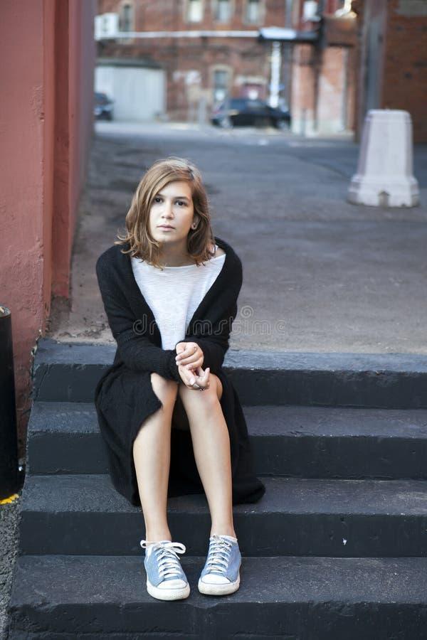 Rozważna dziewczyna w długim czarnym kardiganie i skrótów skrótach siedzi na krokach fotografia royalty free