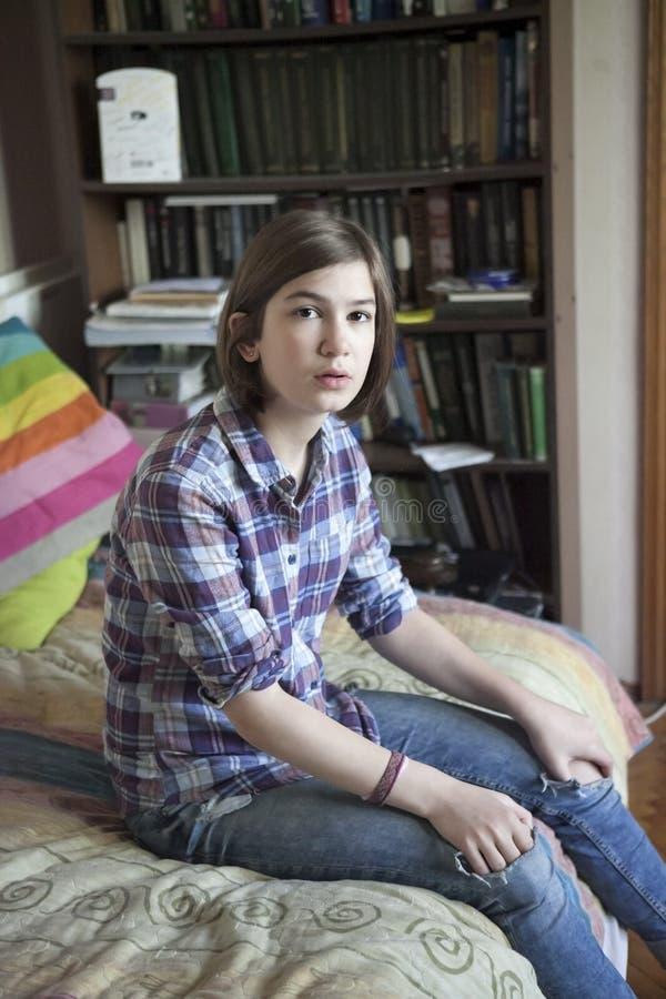 A rozważna dziewczyna w szkockiej kraty koszula siedzi na łóżku przed bookcase obraz royalty free