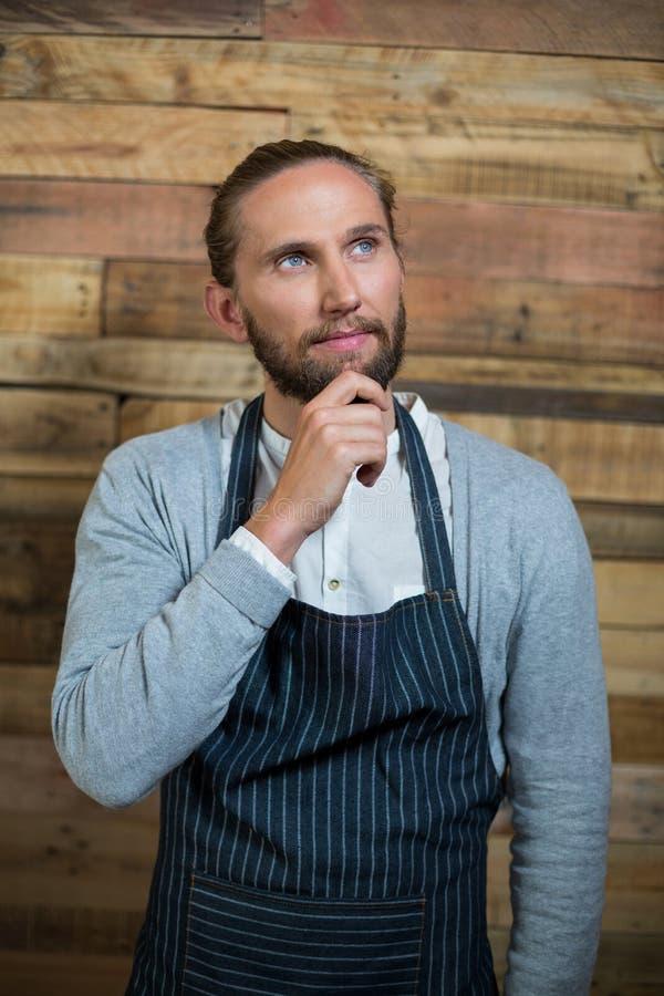 Rozważna kelner pozycja przeciw drewnianej ścianie obrazy royalty free