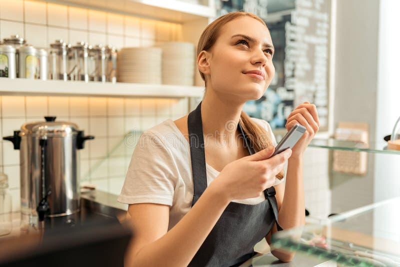 Rozważna kelnerka używa telefon w kawiarni obraz stock