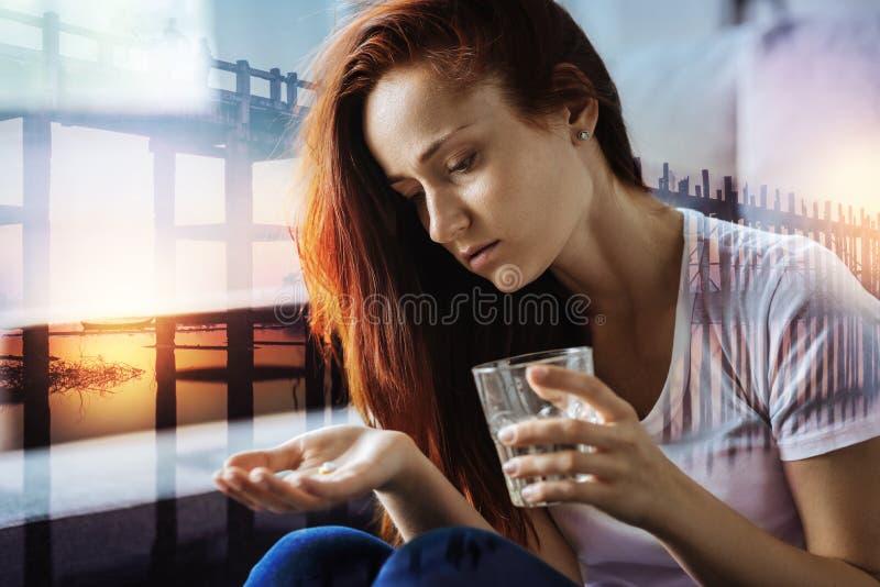 Rozważna kobieta patrzeje pigułki i trzyma szkło woda obrazy royalty free