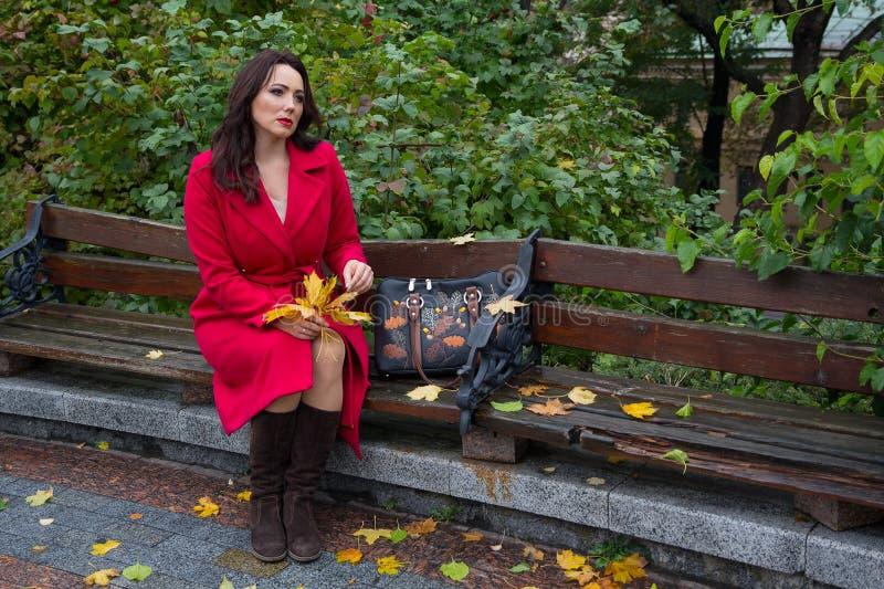 Rozważna kobieta w czerwonym żakiecie na ławce w jesień parku obrazy stock