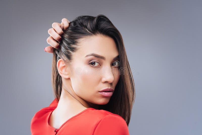 Rozważna młoda kobieta obraca z powrotem podczas gdy dotykający jej włosy fotografia stock