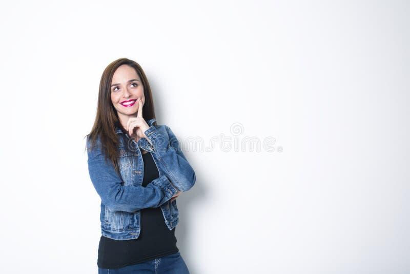 Rozważna młoda kobieta, odizolowywająca nad szarym tłem obraz stock