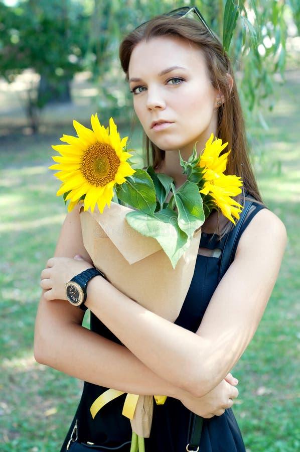 Rozważna młoda kobieta w czerni sukni mienia słonecznikach fotografia stock