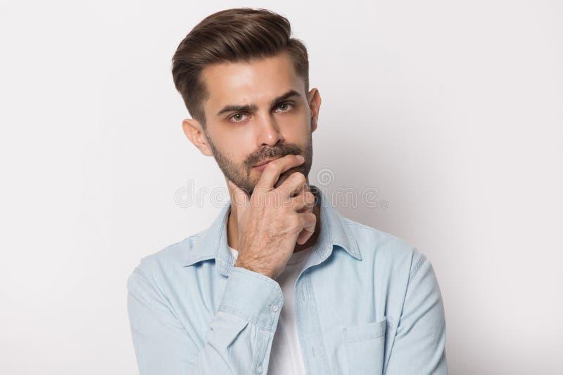 Rozważna młodego człowieka mienia ręka na podbródka czuć wątpliwy zdjęcie royalty free