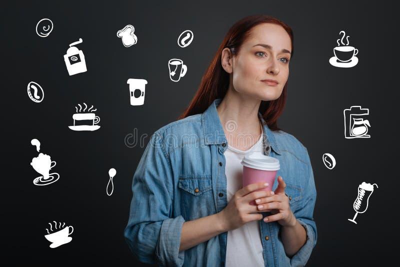 Rozważna młodej kobiety mienia kawa i patrzeć w odległość fotografia royalty free
