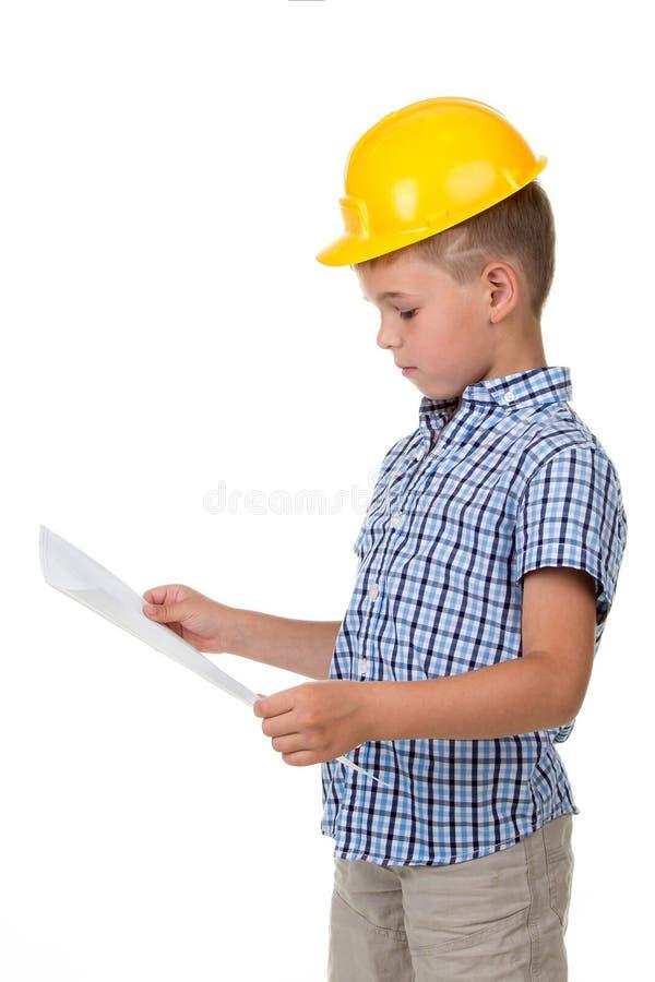 Rozważna mała budowniczy chłopiec trzyma papierowego plan w jego rękach w żółtym hardhat i w kratkę koszula, odosobnionych na bie zdjęcie stock