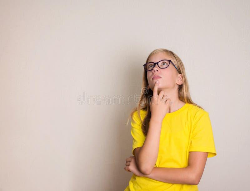 Rozważna nastoletnia dziewczyna w eyeglasses przyglądający up Dosyć przypadkowy thi obrazy stock