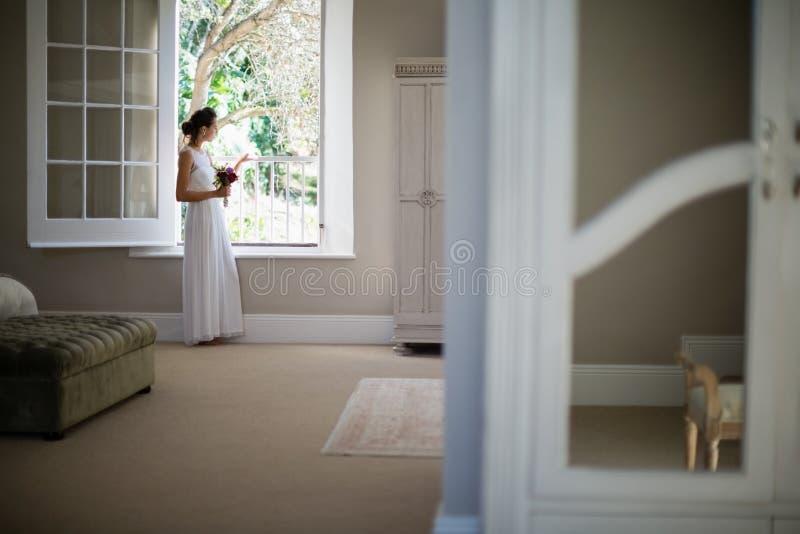 Rozważna panna młoda patrzeje przez okno zdjęcie royalty free