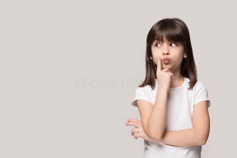 Rozważnej małej dziewczynki przyglądający oddalony główkowanie odizolowywający na popielatym tle obrazy royalty free