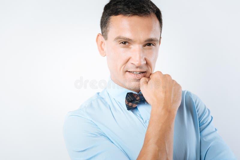 Rozważny ładny mężczyzna trzyma jego podbródek fotografia stock