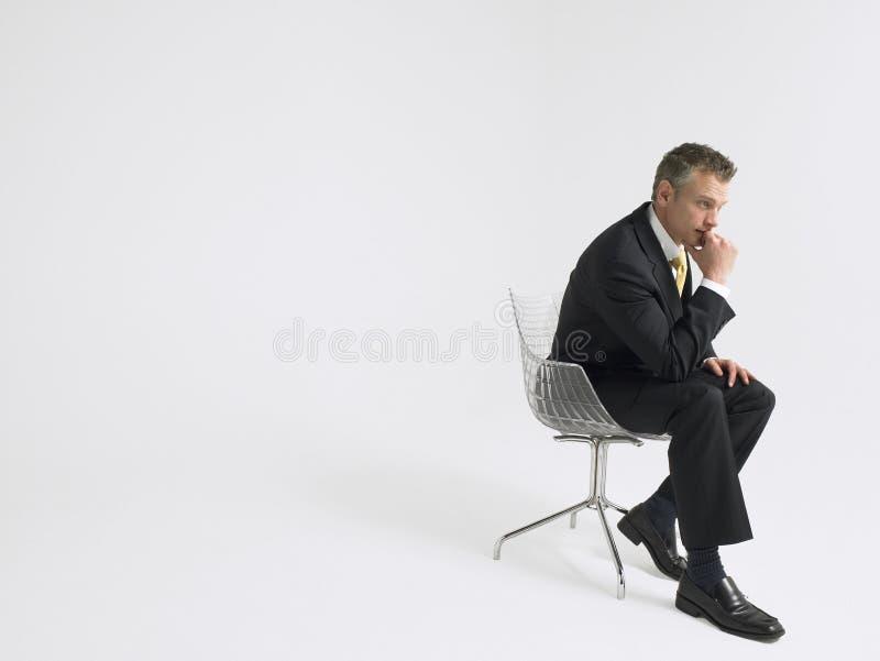 Rozważny biznesmena obsiadanie Przeciw Szaremu tłu zdjęcie royalty free