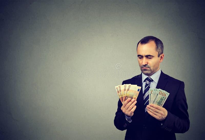 Rozważny biznesowy mężczyzna patrzeje euro i dolara gotówkowych banknoty obraz royalty free