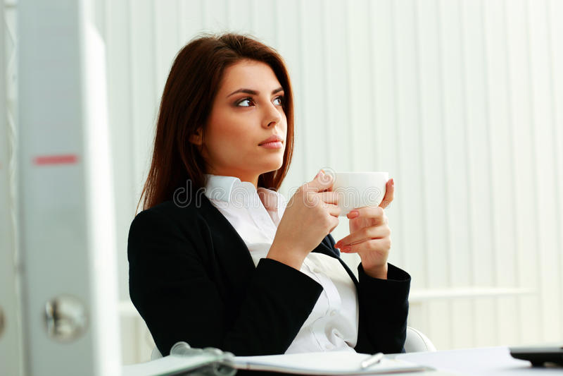 Rozważny bizneswoman trzyma filiżankę i przyglądającego up zdjęcia royalty free