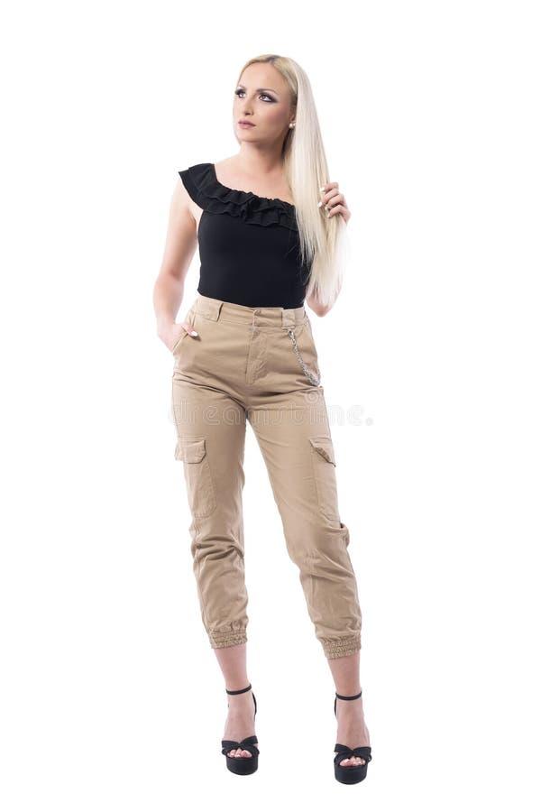 Rozważny blondynki piękno w czerni z ramienia creme i wierzchołka dyszy wzruszającego włosy i patrzeć w dół zdjęcia stock