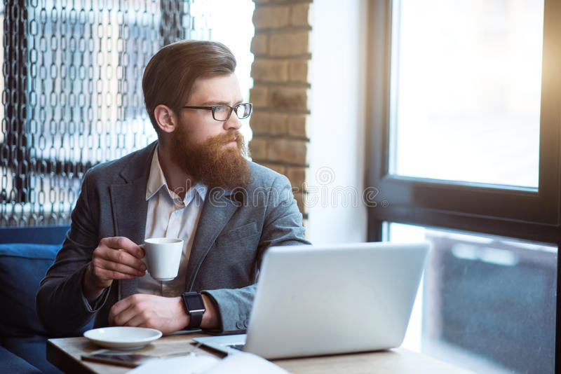 Rozważny brodaty mężczyzna pije kawę zdjęcie royalty free