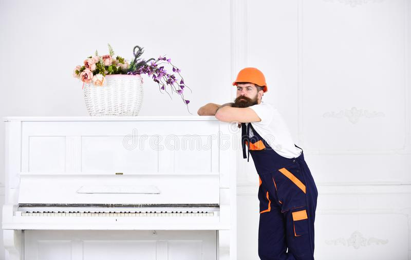 Rozważny facet opiera na wierzchołku rocznika biały pianino z szklaną kwiat wazą odizolowywającą na białym tle brodaty zdjęcia stock