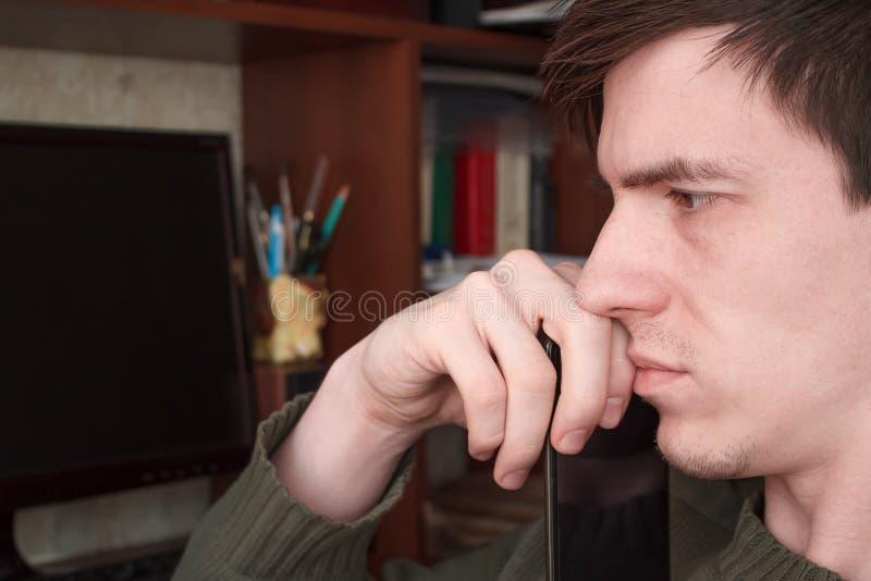 Rozważny facet z smartphone przy jego usta, siedzi przy jego biurkiem na czarnym monitoru tle, zdjęcia royalty free