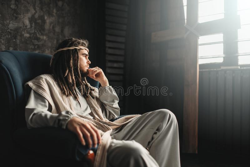 Rozważny jezus chrystus obsiadanie w krześle fotografia royalty free