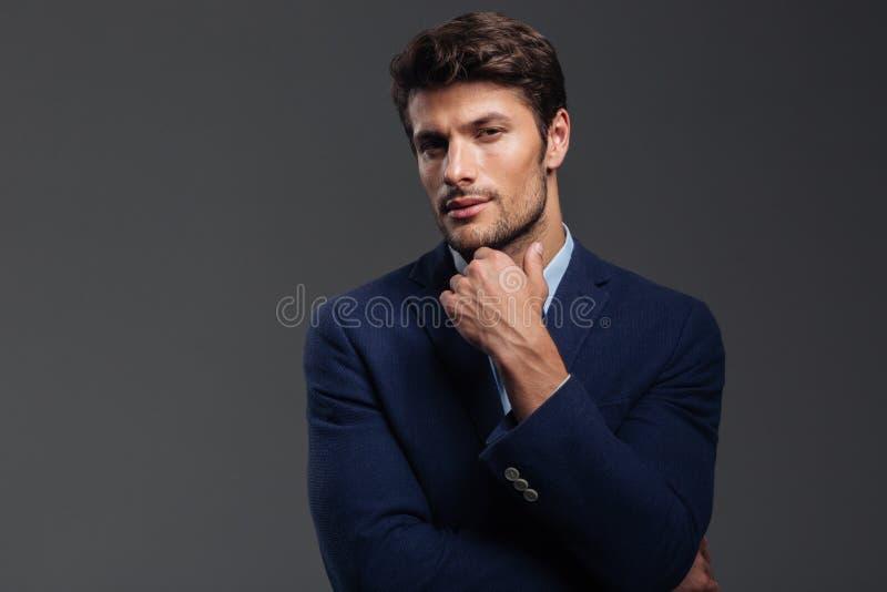 Rozważny młody brunetka mężczyzna myśleć o coś w niebieskiej marynarce zdjęcia royalty free