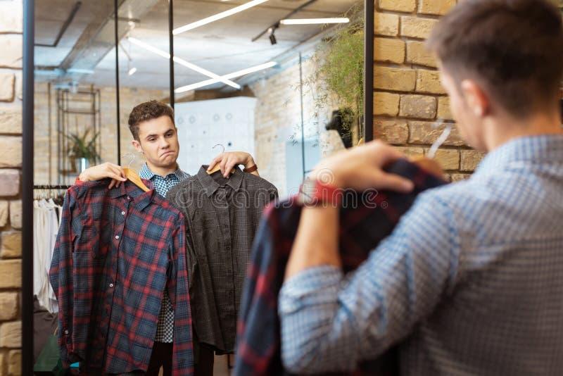 Rozważny młody człowiek patrzeje w lustrze i patrzeje piękne koszula zdjęcia stock