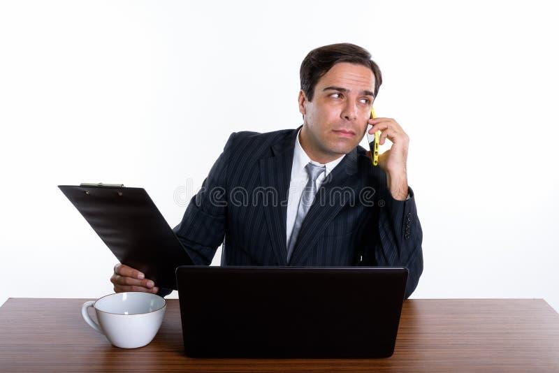 Rozwa?ny m?ody Perski biznesmen opowiada na telefonu kom?rkowego whi fotografia royalty free