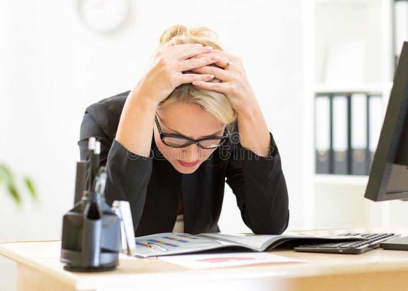 Rozważny pracownik patrzeje biznesowych papiery w biurze fotografia stock