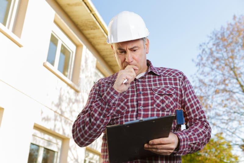 Rozważny pracownika budowniczy w hardhat na tło budowie zdjęcia royalty free