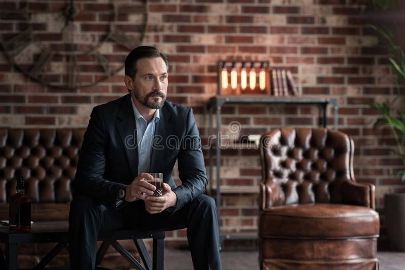 Rozważny przystojny mężczyzna pije whisky obrazy royalty free