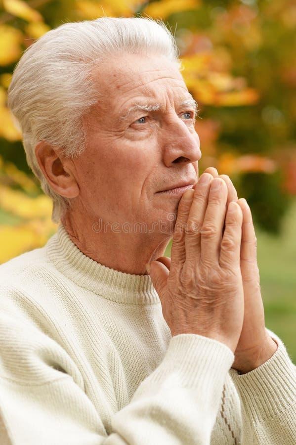 Rozważny starszego mężczyzny modlenie w jesień parku fotografia royalty free