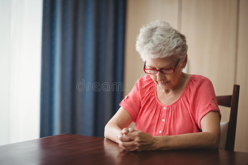 Rozważny starszy kobiety obsiadanie przy stołem zdjęcie royalty free