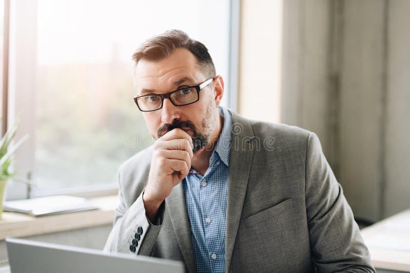 Rozważny w średnim wieku przystojny biznesmen w koszulowym działaniu na laptopie w biurze zdjęcie stock