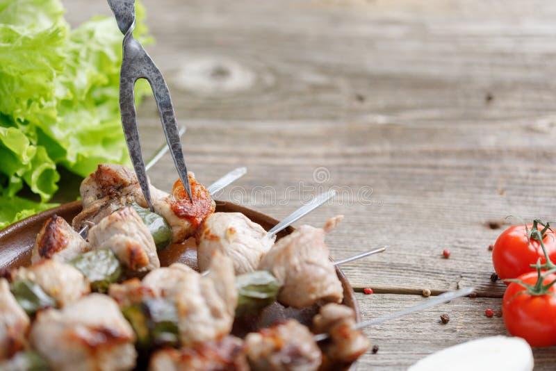 Rozwidlenie wtykający w czułym mięsie gotującym na otwierał ogień soczyści kebabs Życie na drewnianym tle Zakończenie zdjęcia royalty free