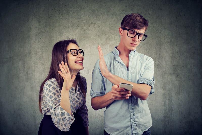 Rozzłościć kobieta próbuje rozpraszać uwagę młodego przystojnego mężczyzna texting na smartphone zdjęcie royalty free