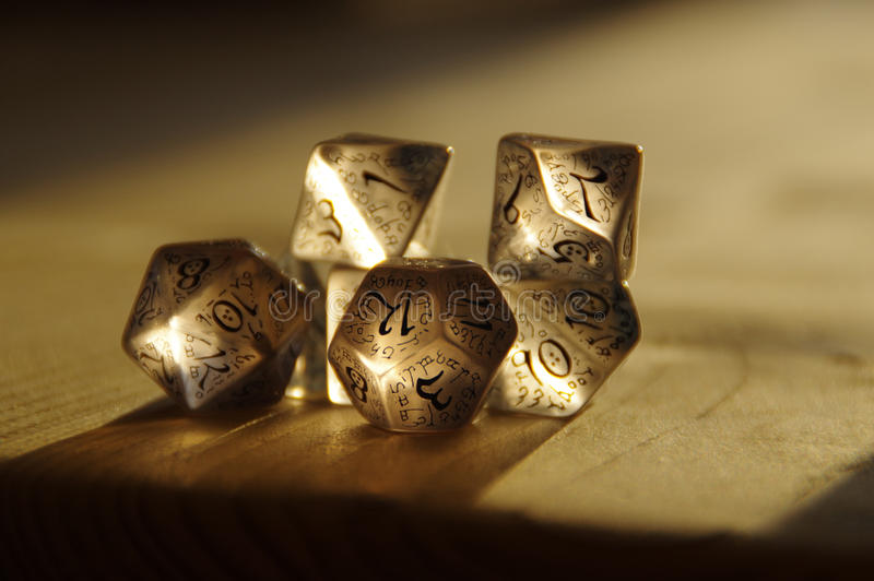 RPG dice for Dungeons and Dragons. Few transparent rpg dice on table highlighted by the sun. D&D - Dungeons and dragons royalty free stock images