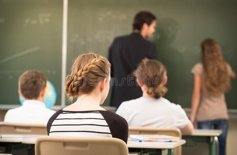RTeacher undervisning eller utbildar på brädet en grupp i schoolr royaltyfri foto