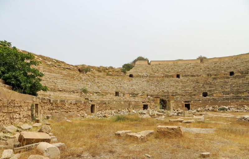 Ruínas da arena romana antiga para gladiadores em Leptis Magna na costa mediterrânea de Líbia imagens de stock royalty free